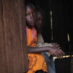 Zipporah's younger sister and brother sit in the shade of their kitchen.